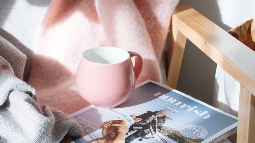 Roze deken met daarop roze mok en tijdschrift
